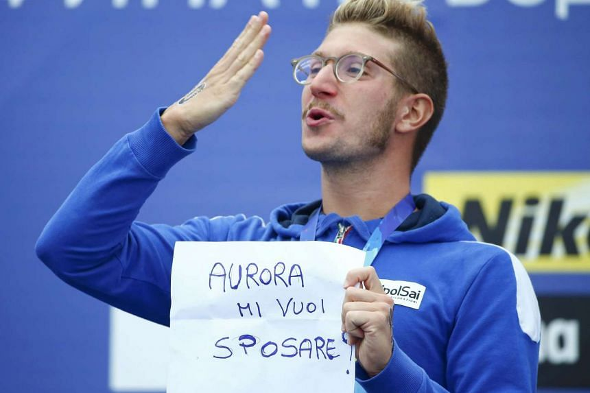 """Italian gold medalist Simone Ruffini blows a kiss into the crowd as he holds up a self-made paper reading """"Aurora do you want to marry me""""."""