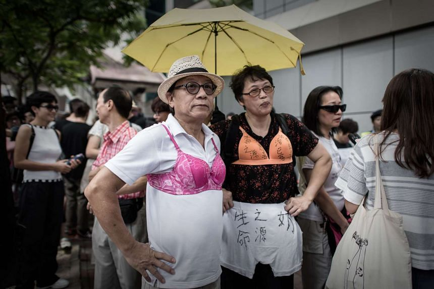 Protesters wear bras during a demonstration outside the police headquarters in Hong Kong on Aug 2, 2015.