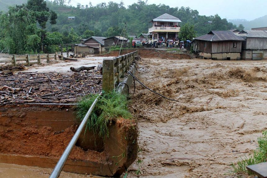 People look at a bridge which was washed away by floodwaters in Thoubal District in Manipur state on Aug 1, 2015.