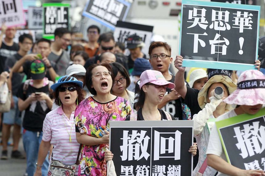 Activists march on the street during a protest in front of the Ministry of Education in Taiwan's capital Taipei on Aug 2, 2015.