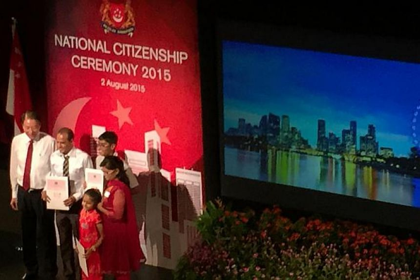Deputy Prime Minister Teo Chee Hean hands out certificates of citizenship on Sunday to new citizens who live in Pasir Ris-Punggol, where he is one of the MPs.