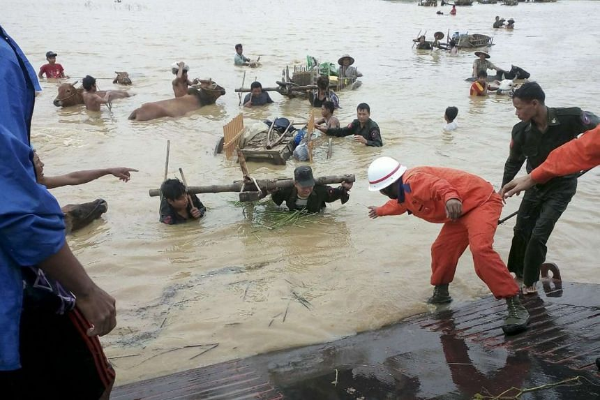 Myanmar rescue workers assist victims with their cattle to flee flooded areas near Thayet township of Magway Region, Myanmar on August 1, 2015.