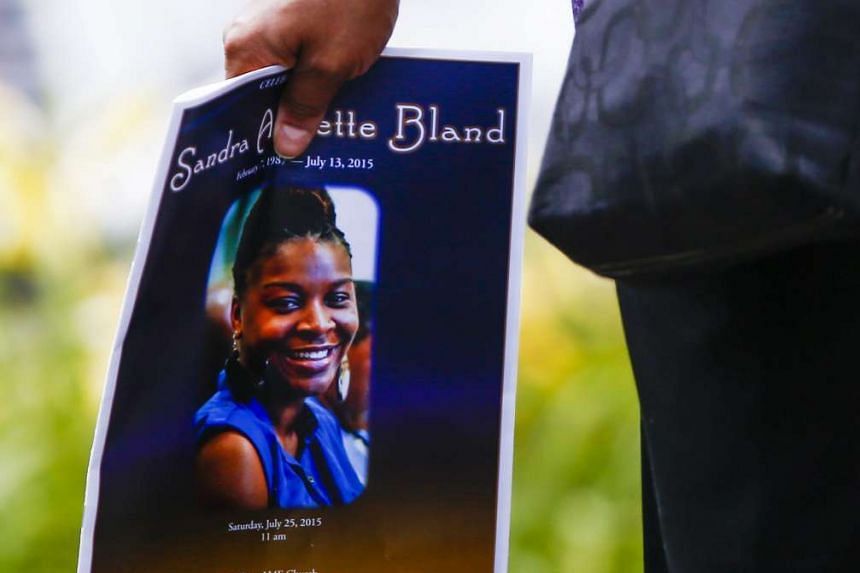 A woman carries a funeral program detailing the life of Sandra Bland following her funeral service.