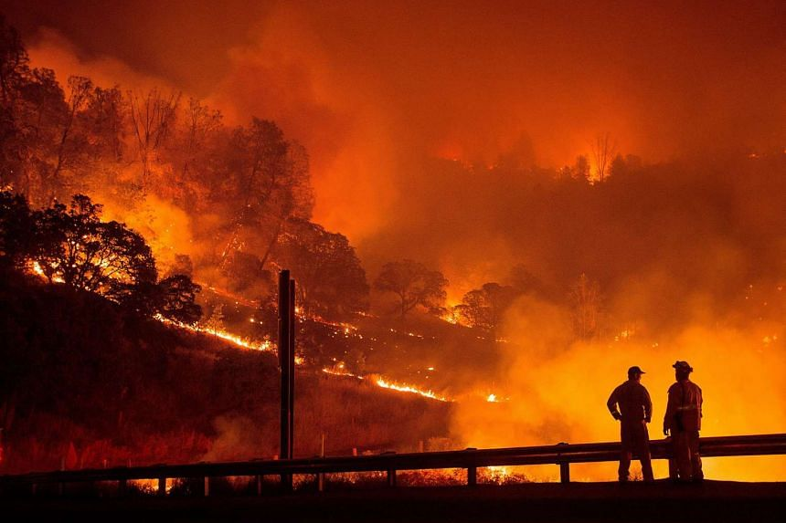 A firefighter helps ignite a backfire while battling the Rocky fire near Clearlake, California, on Aug 2, 2015.