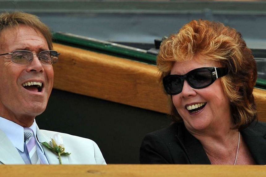 In this file picture taken on July 2, 2009 British singer Sir Cliff Richard (left) and British television personality Cilla Black watch the action on Centre Court during the Women's Semi-Finals of the 2009 Wimbledon Tennis Championships at the All En