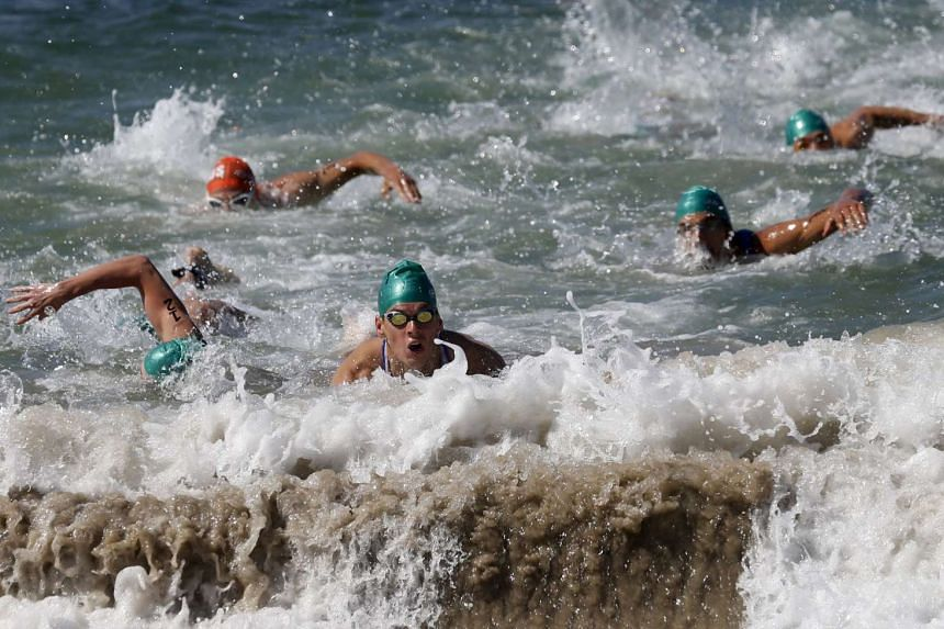 Athletes compete in the swimming leg of the men's triathlon at the ITU World Olympic Qualification event on Copacabana beach in Rio de Janeiro.