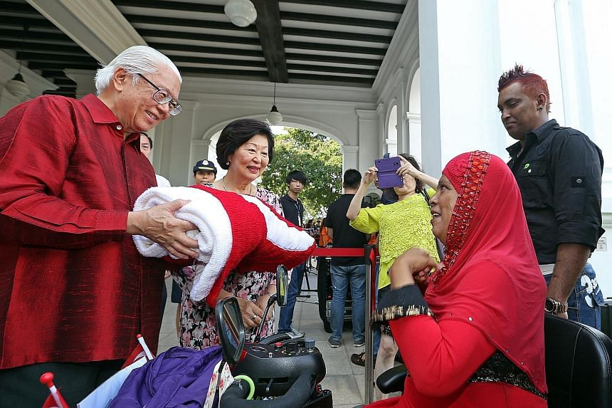 Ms Bashiran Bibi, 59, and her son Abdul Rahim, 36 (right), presenting a 1.3m by 1.8m national flag which she hand-knitted to President Tony Tan Keng Yam and his wife, Mary, at the Istana Open House yesterday. They were among more than 16,000 visitors