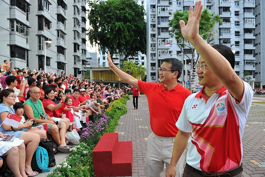 Marine Parade GRC MP Seah Kian Peng (right) and Mr Edwin Tong greeting residents at a National Day celebratory parade in Marine Terrace yesterday.