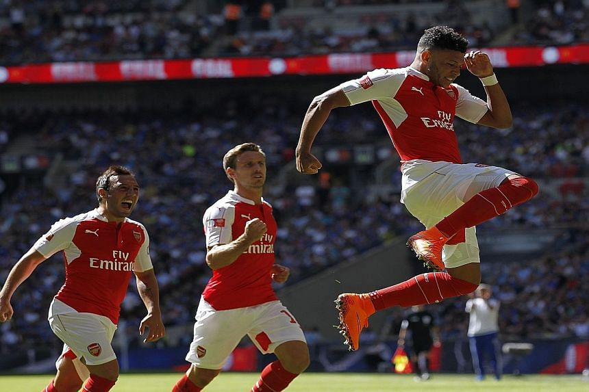 Arsenal's England midfielder Alex Oxlade-Chamberlain (right) celebrates scoring what turned out to be the winning goal in the FA Community Shield against Chelsea.