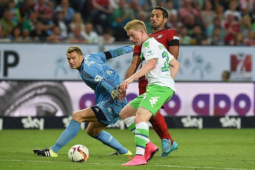 Above: Wolfsburg's Kevin de Bruyne getting the better of Bayern goalkeeper Manuel Neuer but the Belgium international fails to slot home the ball into an open goal at 0-0. Left: Wolfsburg captain Naldo lifting the German Super Cup after Nicklas Bendt