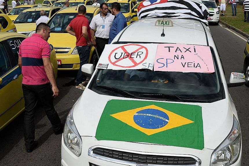 Hundreds of taxi drivers blocking the avenue which links the south and centre of Rio de Janeiro, Brazil, on July 24, to protest against Uber, a mobile phone application to hail taxis.