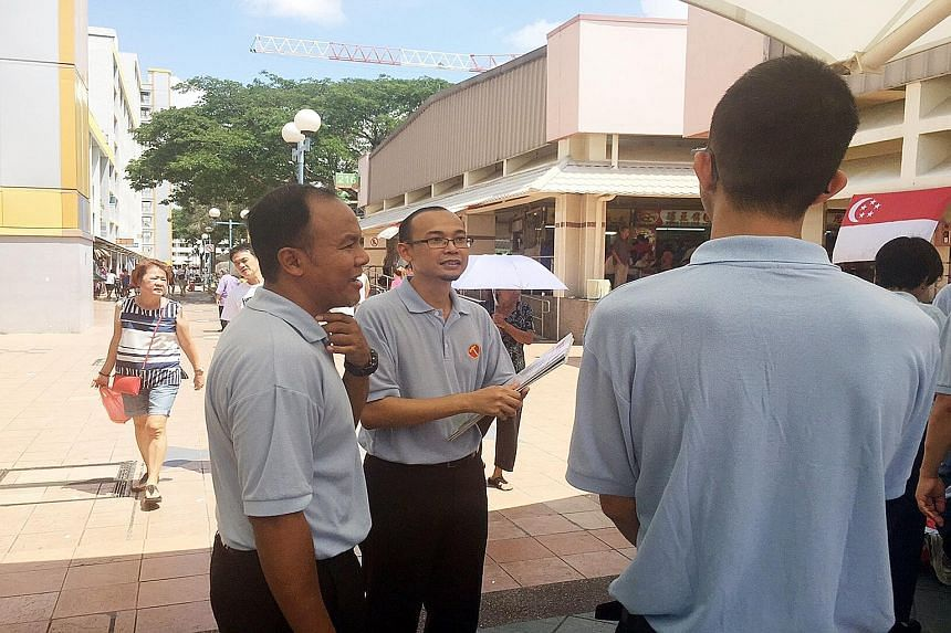 WP member Mohamed Fairoz Shariff (centre, with Aljunied GRC MP Faisal Abdul Manap) at the Fengshan Block 85 Market and Food Centre yesterday.
