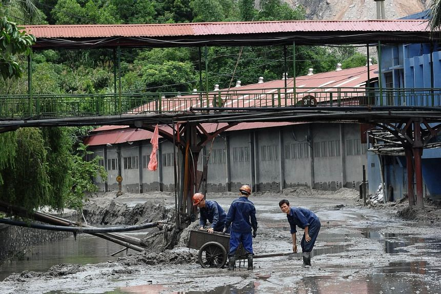 Workers clearing mud at the base of a nearly 300m-high coal-waste pile (background) at the Mong Duong coal mine following heavy rains in Vietnam's northern coastal province of Quang Ninh.