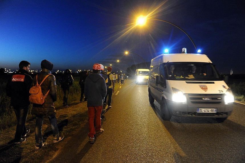 A police vehicle patrols past migrants walking in Coquelles near the northern French port of Calais on Aug 2, 2015.
