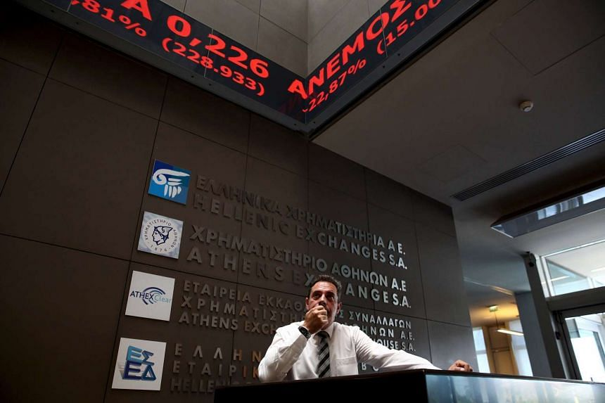 An employee looks on at electronic board displaying stock prices at the entrance of the Athens Stock Exchange, Greece, August 3, 2015. Greece's stock market plunged nearly 22 per cent on Monday when it opened after a five-week shutdown brought on by