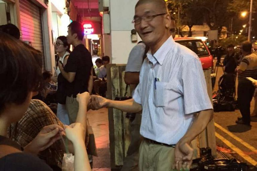 Opposition supporter Kenny Soh, 47, handing out iced milo he bought to media crew outside.