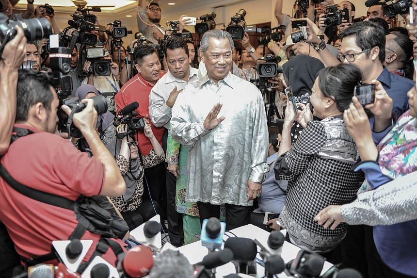 Muhyiddin Yassin (center) waves to journalists as he arrives before a press conference at his residence in Kuala Lumpur on July 29, 2015.