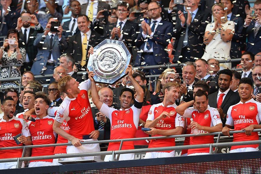 Arsenal's Spanish midfielder Mikel Arteta (centre) lifts the trophy as Arsenal players celebrate after beating Chelsea in the FA Community Shield football match between Arsenal and Chelsea.
