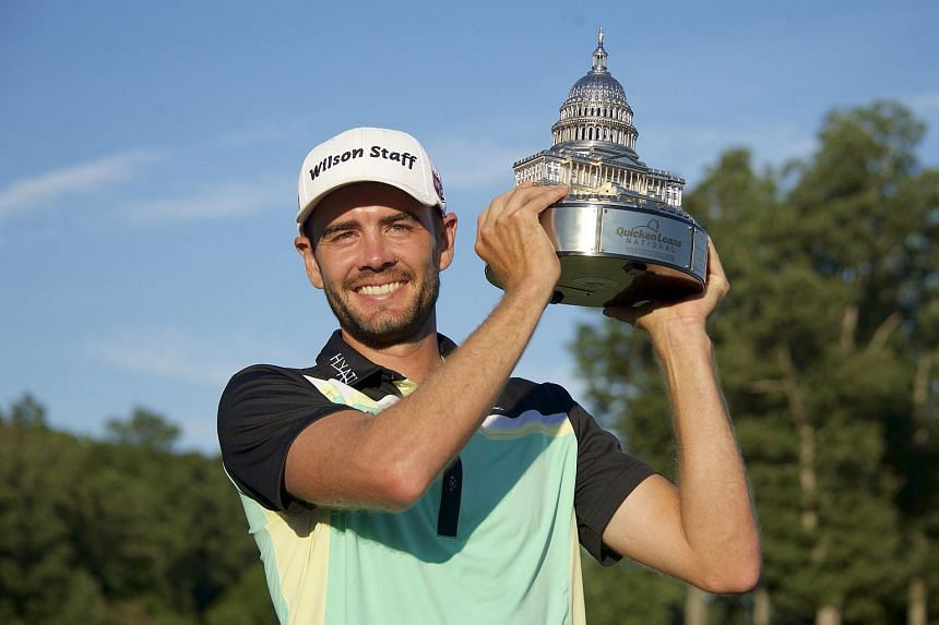 Troy Merritt holds the Quicken Loans National trophy on the 18th hole after winning in the final round of the Quicken Loans National golf tournament at Robert Trent Jones Golf Club.