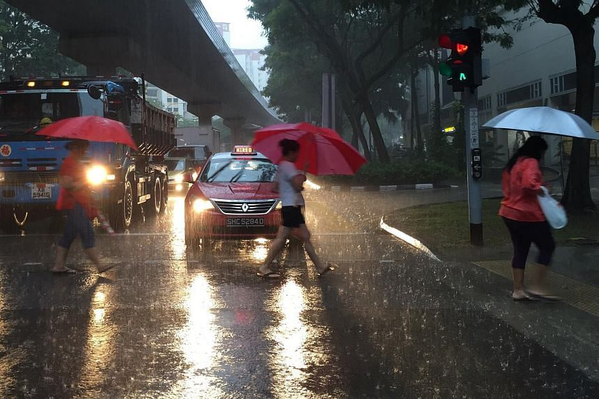 People crossing a road along Rivervale Drive in Sengkang during the heavy downpour on Monday morning.