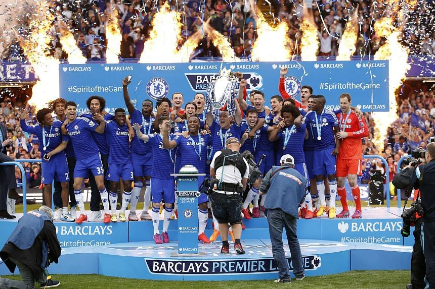 Chelsea's John Terry celebrates with the trophy and teammates after winning the Barclays Premier League.