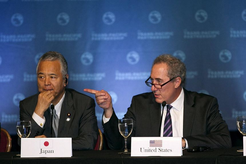 Japanese Economy Minister Akira Amari (left) and US Trade Rep. Michael Fromam participate in a press conference in Maui, Hawaii, where the TPP negotiations took place.