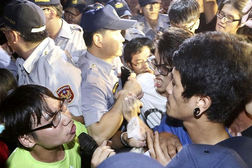 Activists scuffles with police officers during a protest in front of Ministry of Education in Taipei, Taiwan, on July 24, 2015.