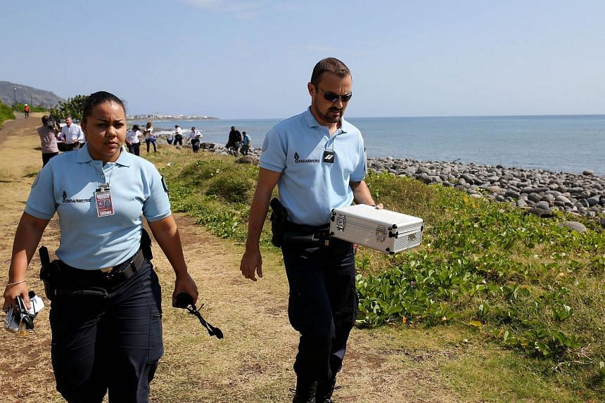 Police officers leave the scene with container holding metallic debris found on a beach in Saint-Denis on the French Reunion Island in the Indian Ocean on August 2, 2015.