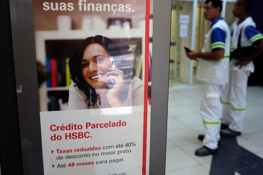 Two customers stand at a HSBC bank cash dispenser, following the announcement of the bank to close HSBC Brazil.