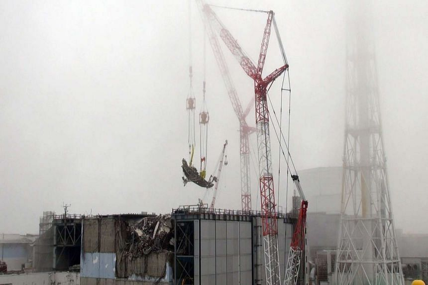 A large amount of debris is removed by a crane at the unit three reactor building of TEPCO's Fukushima Dai-ichi nuclear power plant near Okuma in Fukushima prefecture.