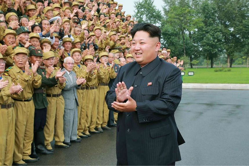 North Korean leader Kim Jong Un (right) attending a photo session with the participants in the Fourth National Conference of War Veterans in front of the Fatherland Liberation War Martyrs Cemetery in Pyongyang.
