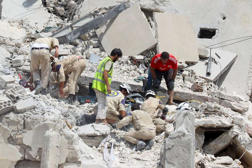 Civil defence members search for survivors under the rubble after a Syrian army fighter jet crashed into a busy marketplace in the rebel-held north-western town of Ariha on Aug 3, 2015.