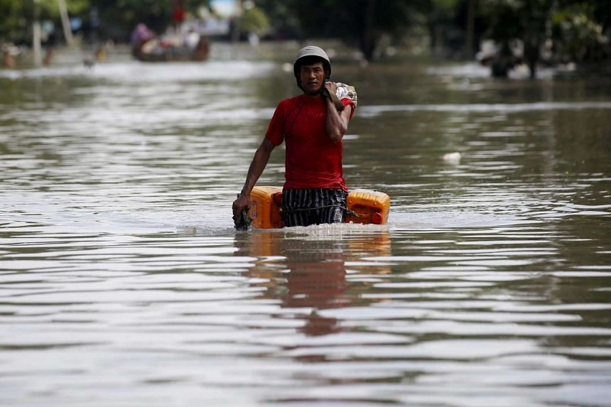 Local man carries his belongings as he wades through a flooded road in Kale township of Sagaing Region, Myanmar, on Aug 3, 2015.