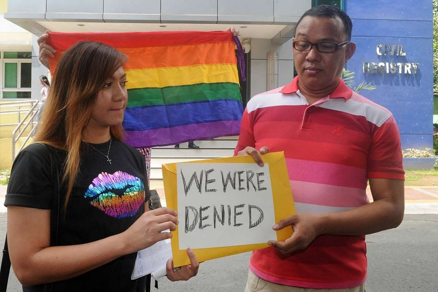 Maria Arlyn Ibanez (left) and pastor Crescencio Agbayani (right) hold a placard in protest outside the Civil Registry Office in Manila on Aug 3, 2015, after their application for same-sex marriage licenses for their respective partners were denied.