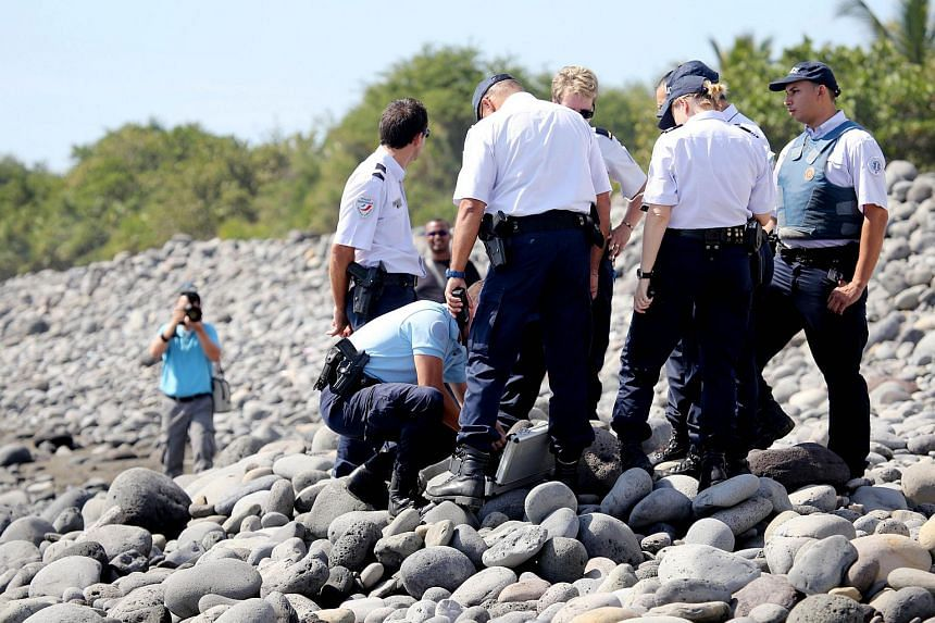 Police officers inspect metallic debris found on a beach in Saint-Denis on the French Reunion Island in the Indian Ocean on Aug 2, 2015, close to where where a Boeing 777 wing part believed to belong to missing flight MH370 washed up last week.