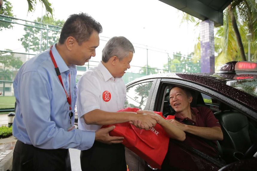 Mr Lim Choon Seng, 67, receives his SG50 goodie bag from Mr Ang Hin Kee. Mr Lim has been a driver with SMRT since November 2011.