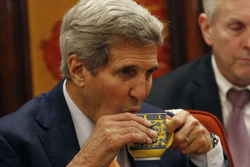 US Secretary of State John Kerry drinks tea during a meeting with Chinese Premier Li Keqiang at Zhongnanhai Leadership Compound in Beijing on May 16, 2015.
