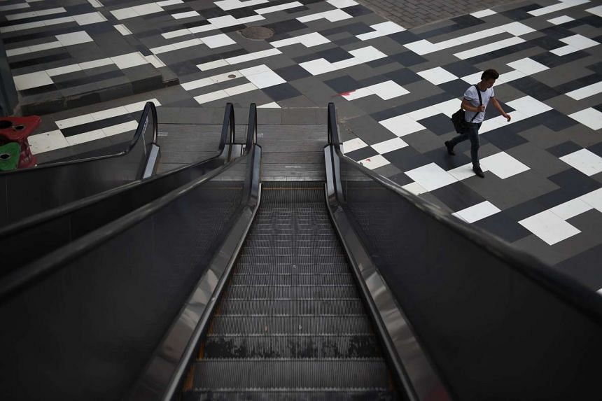 A man walks past an escalator at a shopping mall in Beijing on June 17, 2015. In recent months, China has seen a spate of horrific safety lapses that caused one woman to plunge into an escalator pit after a loose footplate gave way and another steppi