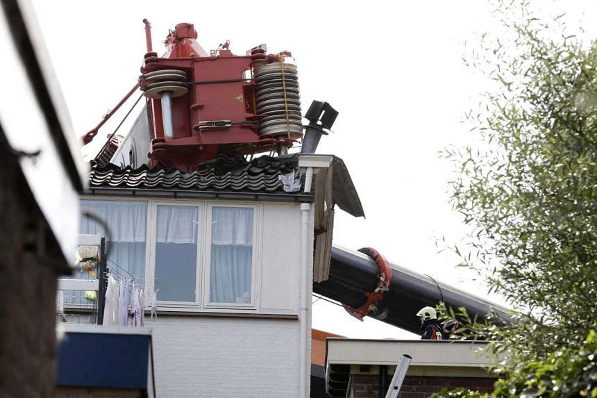 Two cranes have fallen onto a row of houses in Alphen aan den Rijn, the Netherlands, Aug 3. The cranes were being used to restore a bridge in the city when they tipped over.
