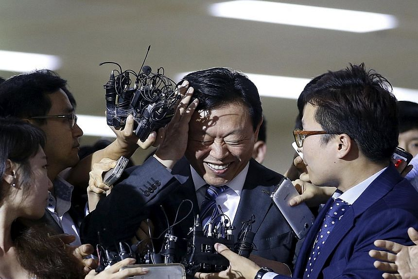Mr Shin Dong Bin (centre), the younger son of Lotte founder Shin Kyuk Ho, surrounded by the media in Seoul yesterday.