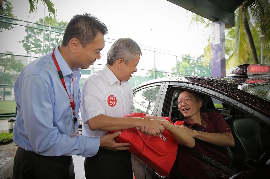 Mr Lim Choon Seng, 67, receiving the SG50 goodie bag from Mr Ang Hin Kee (centre), the executive adviser of the National Taxi Association, and Mr Tony Heng, general manager of SMRT Taxis.