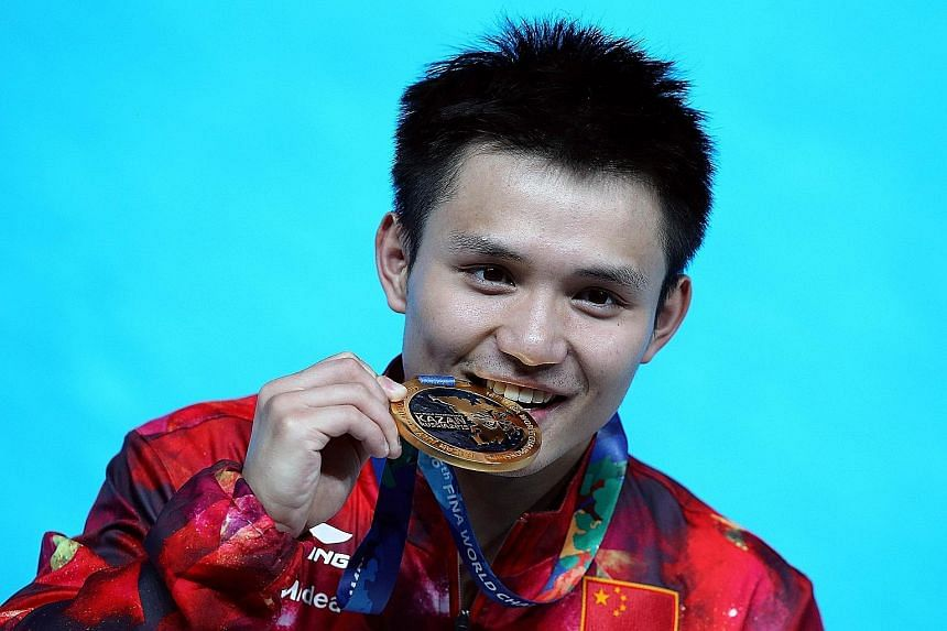 Qiu Bo of China bites his gold medal after winning the men's 10m platform final.