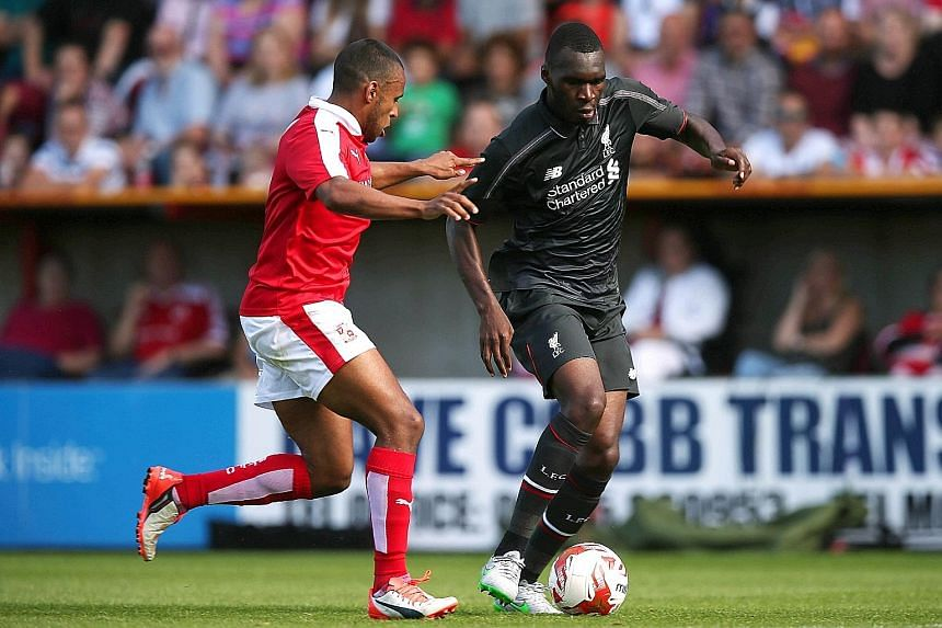 Christian Benteke (right), in action against Swindon, could be the answer to Liverpool's problem of scoring only 52 goals in the EPL last term.