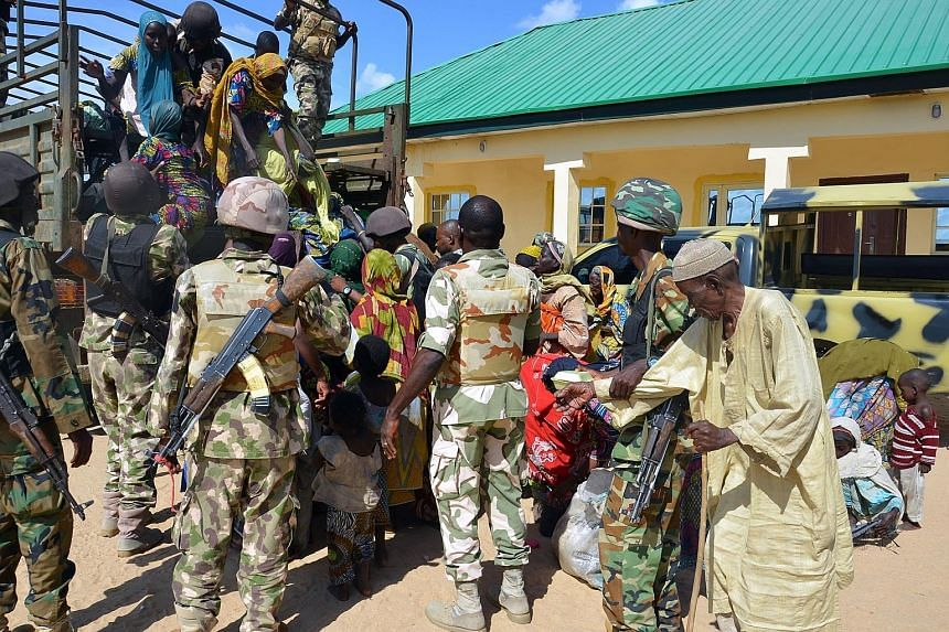 Soldiers from the Nigerian military assisting the people rescued from Boko Haram camps in Maiduguri in north-eastern Nigeria.