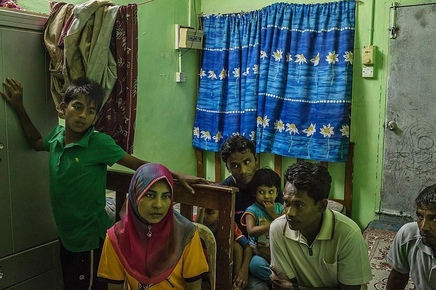 Ms Shahidah Yunus with husband Dil Muhammad Hussan (second from right) in the Penang house they share with 17 other migrants.