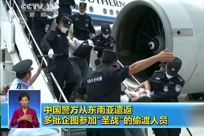 Uighurs being deported from Thailand are seen brought off an airplane by police in China.