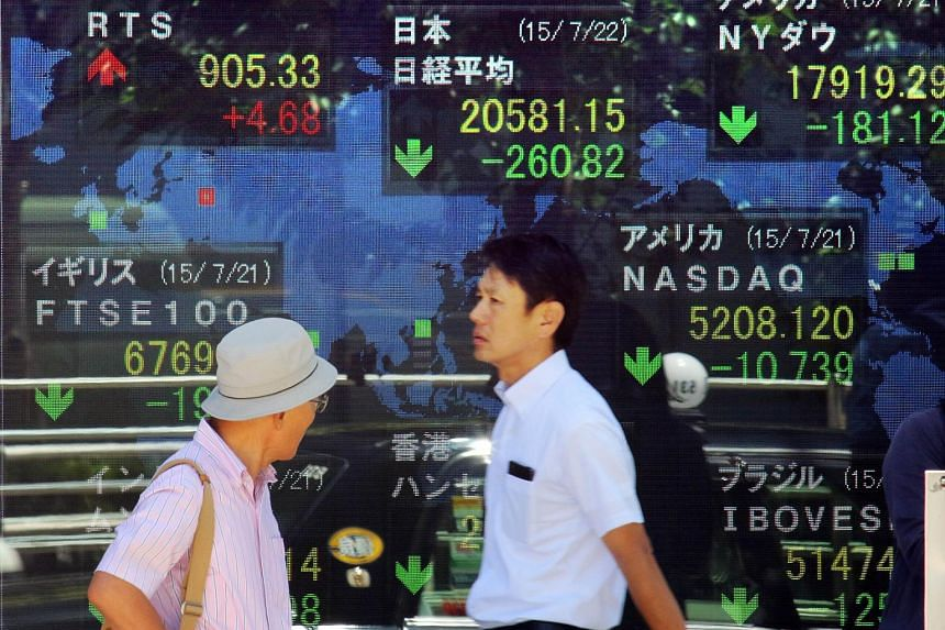 Pedestrians passing by a share prices board in Tokyo.