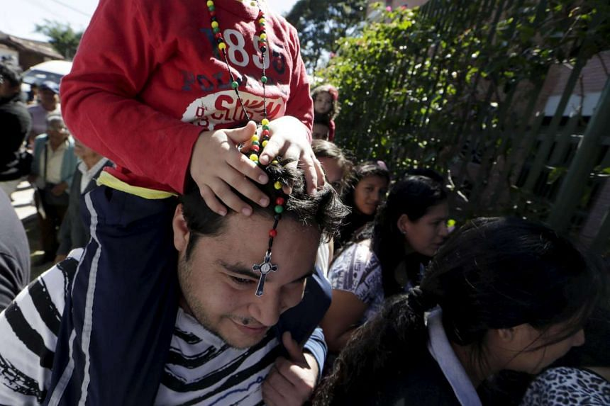 A father carries his son on his shoulders in hope of receive a blessing for his child outside a church.