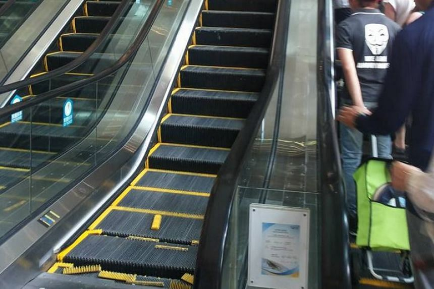 Mall-goers looking at the damaged escalator as they take the opposite escalator up to the second floor.