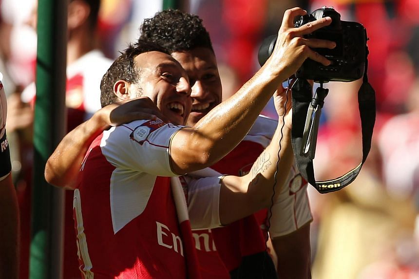 Arsenal's Santi Cazorla (left) and Alex Oxlade-Chamberlain celebrate by taking a selfie at the end of the FA Community Shield match between Chelsea and Arsenal.